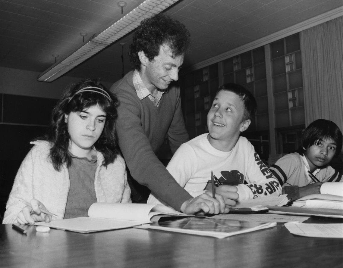 A teacher helps a student in a Social Studies classroom (1984.)